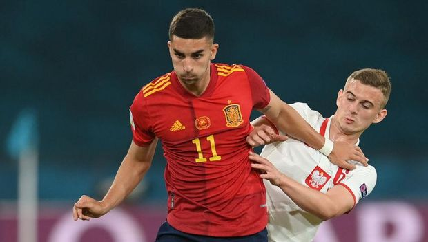 SEVILLE, SPAIN - JUNE 19: Ferran Torres of Spain battles for possession with Kacper Kozlowski of Poland during the UEFA Euro 2020 Championship Group E match between Spain and Poland at Estadio La Cartuja on June 19, 2021 in Seville, Spain. (Photo by David Ramos/Getty Images)