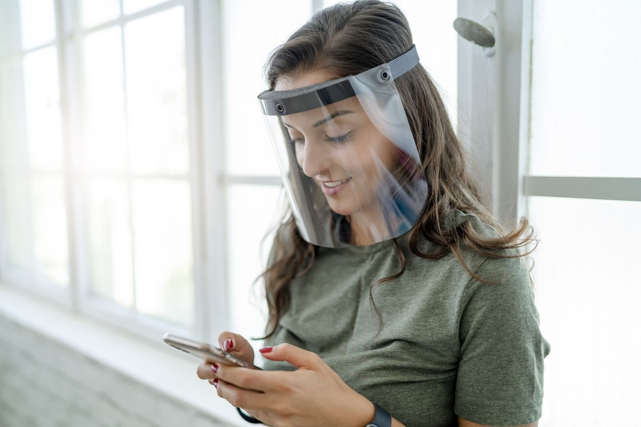 Young woman working with face shield in the office during COVID-19 pandemic