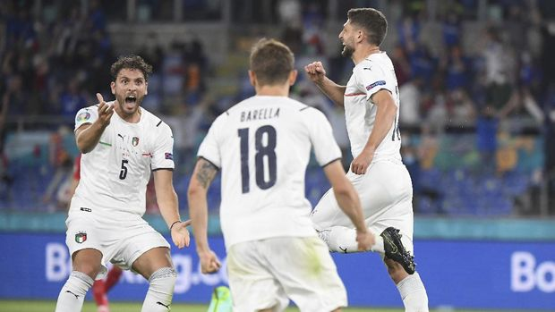 Italy's Manuel Locatelli, left, celebrates with Italy's Nicolo Barella, center, and Italy's Domenico Berardi after Turkey's Merih Demiral scores an own goal during the Euro 2020 soccer championship group A match between Italy and Turkey at the Olympic stadium in Rome, Friday, June 11, 2021. (Alberto Lingria/Pool Photo via AP)