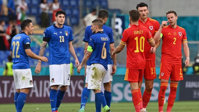 ROME, ITALY - JUNE 20: Kieffer Moore of Wales interacts with team mates Aaron Ramsey and Chris Gunter as Giacomo Raspadori, Alessandro Bastoni and Marco Verratti of Italy celebrates their sides victory after the UEFA Euro 2020 Championship Group A match between Italy and Wales at Olimpico Stadium on June 20, 2021 in Rome, Italy. (Photo by Andreas Solaro - Pool/Getty Images)