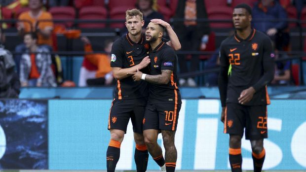 Memphis Depay of the Netherlands, center, celebrates with Matthijs de Ligt, left, and Denzel Dumfries, after scoring his side's opening goal during the Euro 2020 soccer championship group F match between North Macedonia and Netherlands, at the Johan Cruyff ArenA in Amsterdam, Netherlands, Monday, June 21 2021. (Kenzo Tribouillard/Pool via AP)