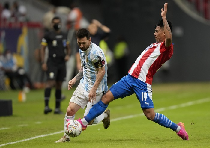 Argentinas Lionel Messi, left, and Paraguays Santiago Arzamendia battle for the ball during a Copa America soccer match at the National stadium in Brasilia, Brazil, Monday, June 21, 2021. (AP Photo/Ricardo Mazalan)