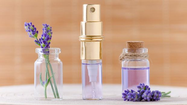 lavender water in glass bottles and fresh lavender flowers for relax on brown background, selective focus