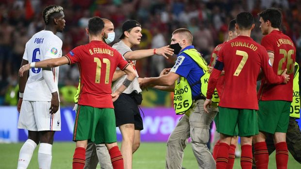 BUDAPEST, HUNGARY - JUNE 23: A pitch invader is tackled by security as he tries to get to Cristiano Ronaldo of Portugal following  the UEFA Euro 2020 Championship Group F match between Portugal and France at Puskas Arena on June 23, 2021 in Budapest, Hungary. (Photo by Franck Fife - Pool/Getty Images)