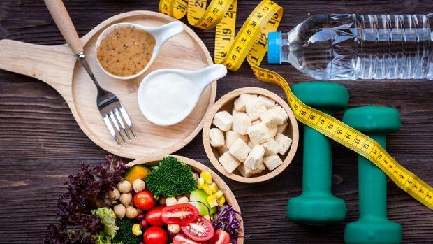 Ensalada de verduras frescas y alimentos saludables para equipos deportivos para mujeres que adelgazan con grifo de medida para bajar de peso sobre fondo de madera.  Concepto de deporte saludable