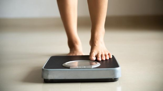 Female leg stepping on weigh scales.  Healthy lifestyle, food and sports concept.