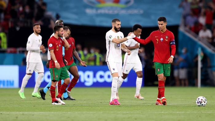 BUDAPEST, HUNGARY - JUNE 23: Karim Benzema of France interacts with Cristiano Ronaldo of Portugal during the UEFA Euro 2020 Championship Group F match between Portugal and France at Puskas Arena on June 23, 2021 in Budapest, Hungary. (Photo by Alex Pantling/Getty Images)