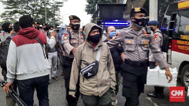 Simpatisan mantan Imam Besar FPI Rizieq Shihab diamankan aparat di depan Pengadilan Negeri Jakarta Timur (PN Jaktim), Kamis (24/6)
