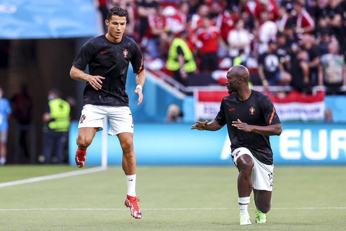 Portugal's Cristiano Ronaldo, left, and teammate Danilo Pereira warm up prior the Euro 2020 soccer championship group F match between Hungary and Portugal at the Ferenc Puskas stadium in Budapest, Hungary, Tuesday, June 15, 2021. (Bernadett Szabo/Pool via AP)