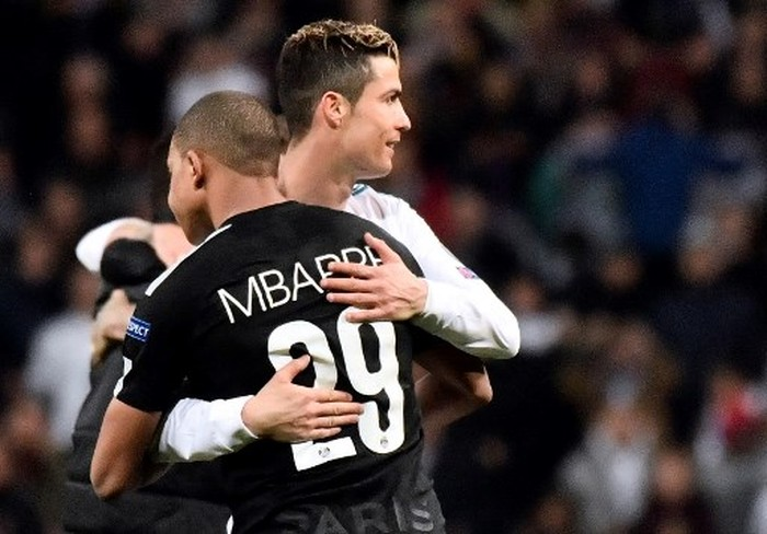 Real Madrid's Portuguese forward Cristiano Ronaldo (R) hugs Paris Saint-Germain's French forward Kylian Mbappe during the UEFA Champions League round of sixteen first leg football match Real Madrid CF against Paris Saint-Germain (PSG) at the Santiago Bernabeu stadium in Madrid on February 14, 2018. (Photo by CHRISTOPHE SIMON / AFP)