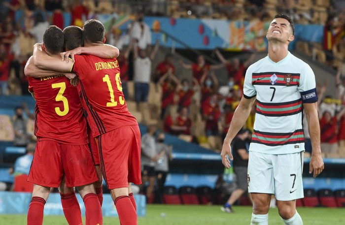Portugals Cristiano Ronaldo, right, reacts as Belgium players celebrate following the Euro 2020 soccer championship round of 16 match between Belgium and Portugal at La Cartuja stadium, Seville, Spain, Sunday, June 27, 2021. (Lluis Gene/Pool Photo via AP)