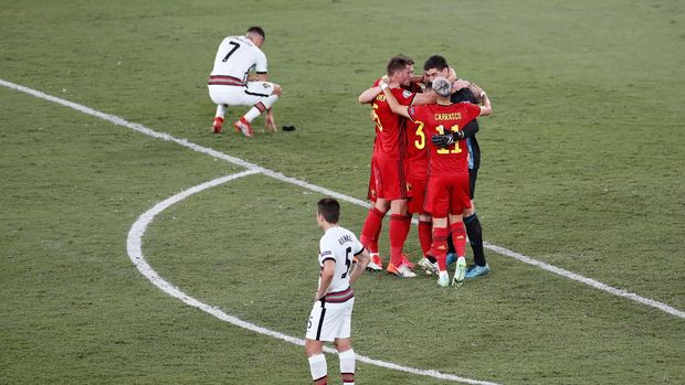 SEVILLE, SPAIN - JUNE 27: Players of Belgium celebrates their side's victory as Cristiano Ronaldo and Raphael Guerreiro of Portugal look dejected after the UEFA Euro 2020 Championship Round of 16 match between Belgium and Portugal at Estadio La Cartuja on June 27, 2021 in Seville, Spain. (Photo by Jose Manuel Vidal - Pool/Getty Images)