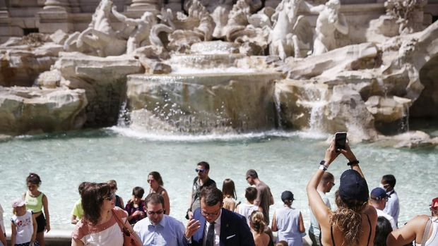 People gather in front of the Trevi fountain in Rome, Monday, June 28, 2021. Italians took off their face masks and breathed a huge sigh of relief on Monday as the government-imposed requirement on mask wearing outdoors was lifted. Italian Health Minister Roberto Speranza made the decision last week to lift the outdoor mask-wearing requirement on advice from Italy's Scientific Technical Committee (CTS) that made the decision based on the stabilisation of Italy Covid-19 indicators. (Cecilia Fabiano/LaPresse via AP)