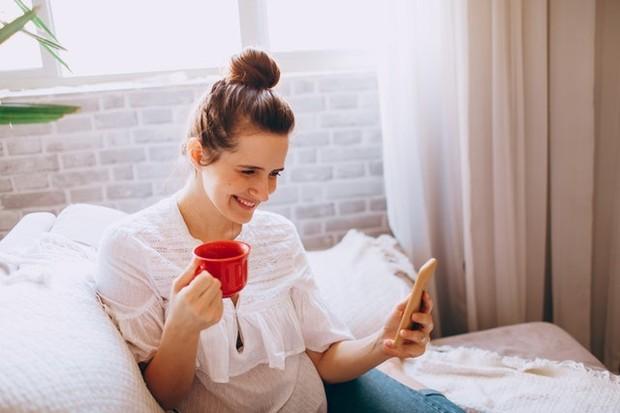 wanita memegang handphone