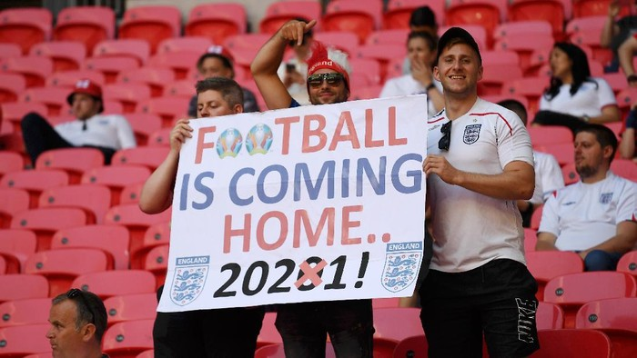 LONDON, ENGLAND - JUNE 13: England fans with a sign saying Football is coming home 2021 prior to the UEFA Euro 2020 Championship Group D match between England and Croatia at Wembley Stadium on June 13, 2021 in London, England. (Photo by Andy Rain - Pool/Getty Images)