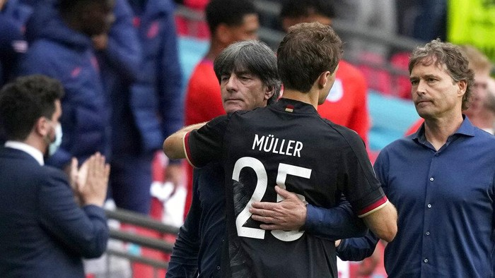 Germanys manager Joachim Loew embraces Germanys Thomas Mueller at the end of the Euro 2020 soccer championship round of 16 match between England and Germany at Wembley stadium in London, Tuesday, June 29, 2021. England won 2-0. (AP Photo/Frank Augstein, Pool)