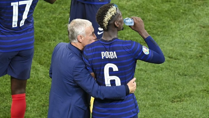 Frances manager Didier Deschamps embraces Paul Pogba during the break in extra time during the Euro 2020 soccer championship round of 16 match between France and Switzerland at National Arena stadium, Bucharest, Romania, Tuesday, June 29, 2021. (Daniel Mihailescu/Pool Photo via AP)