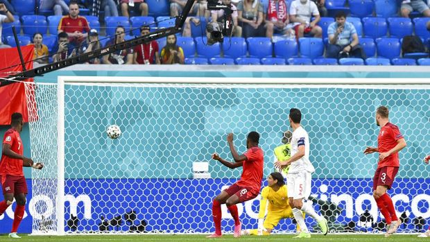 The ball shot by Spain's Jordi Alba goes into the net for Spain to score its opening goal during the Euro 2020 soccer championship quarterfinal match between Switzerland and Spain, at the Saint Petersburg stadium in Saint Petersburg, Friday, July 2, 2021. (Kirill Kudryavtsev, Pool via AP)