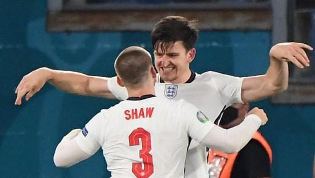 England's defender Harry Maguire (back) celebrates with England's defender Luke Shaw after scoring the second goal during the UEFA EURO 2020 quarter-final football match between Ukraine and England at the Olympic Stadium in Rome on July 3, 2021. (Photo by ALBERTO LINGRIA / POOL / AFP)