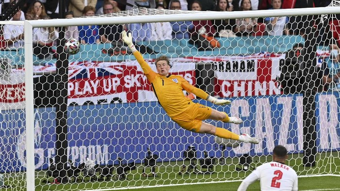 Englands goalkeeper Jordan Pickford is airborne as he fails to stop a goal from Denmarks Mikkel Damsgaard during the Euro 2020 soccer championship semifinal between England and Denmark at Wembley stadium in London, Wednesday, July 7, 2021. (Justin Tallis/Pool Photo via AP)