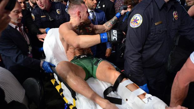 Jul 10, 2021; Las Vegas, Nevada, USA; Conor McGregor is carried off a stretcher following an injury suffered against Dustin Poirier during UFC 264 at T-Mobile Arena. Mandatory Credit: Gary A. Vasquez-USA TODAY Sports