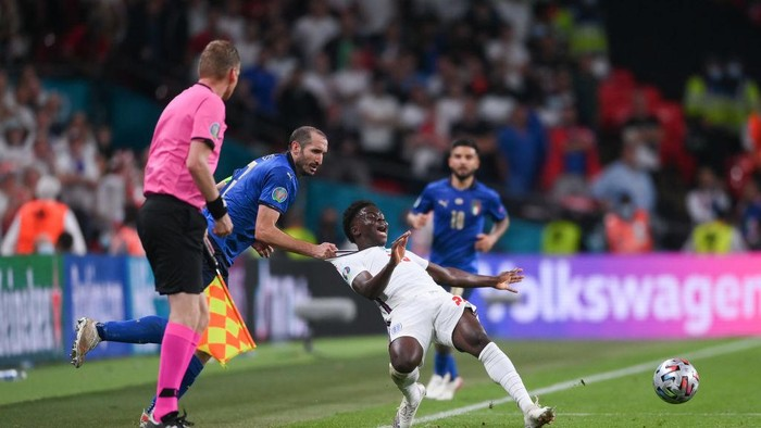 LONDON, ENGLAND - JULY 11: Bukayo Saka of England is fouled by Giorgio Chiellini of Italy during the UEFA Euro 2020 Championship Final between Italy and England at Wembley Stadium on July 11, 2021 in London, England. (Photo by Laurence Griffiths/Getty Images)