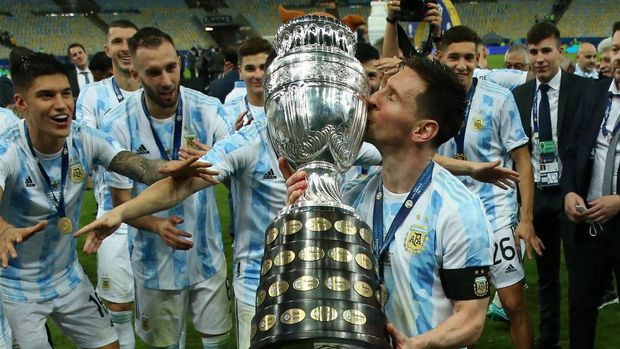 RIO DE JANEIRO, BRAZIL - JULY 10: Lionel Messi of Argentina kisses the trophy as he celebrates with teammates after winning the final of Copa America Brazil 2021 between Brazil and Argentina at Maracana Stadium on July 10, 2021 in Rio de Janeiro, Brazil. (Photo by Alexandre Schneider/Getty Images)