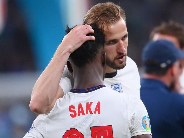 LONDON, ENGLAND - JULY 11: Bukayo Saka of England is consoled by teammate Harry Kane following defeat in the UEFA Euro 2020 Championship Final between Italy and England at Wembley Stadium on July 11, 2021 in London, England. (Photo by Laurence Griffiths/Getty Images)