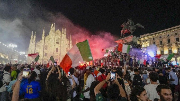 Italys fans celebrate in front of the Duomo cathedral in Milan, Monday, July 12, 2021, after Italy beat England to win the Euro 2020 soccer championships in a final played at Wembley stadium in London. Italy beat England 3-2 in a penalty shootout after a 1-1 draw. (AP Photo/Luca Bruno)