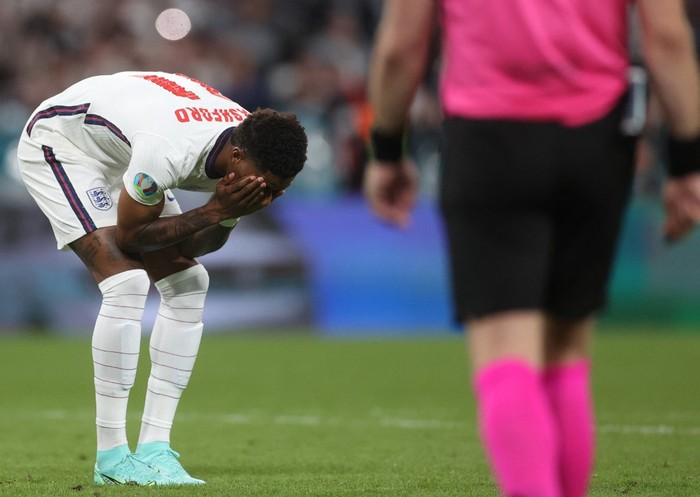 Englands forward Marcus Rashford (L) reacts after failing to score in the penalty shootout during the UEFA EURO 2020 final football match between Italy and England at the Wembley Stadium in London on July 11, 2021. (Photo by CARL RECINE / POOL / AFP)