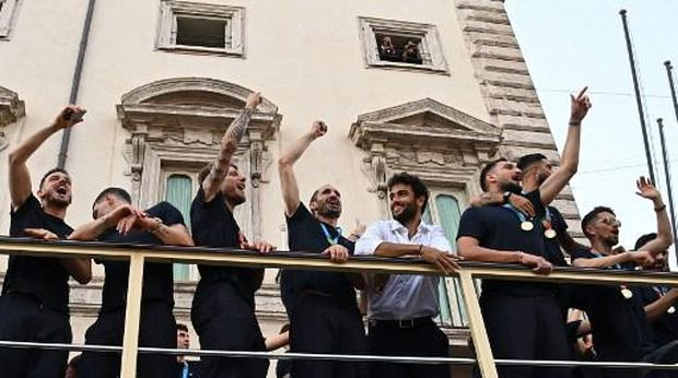 Players of Italy's national football team (From L) Italy's defender Alessandro Florenzi, Italy's forward Andrea Belotti, Italy's forward Ciro Immobile, Italy's defender Giorgio Chiellini parade with the UEFA EURO 2020 trophy, along with Italy's tennis player and Wimbledon's 2021 finalist, Matteo Berrettini (C-R) on a double decker bus on Via del Corso in Rome on July 12, 2021, a day after Italy won the UEFA EURO 2020 final football match between Italy and England. (Photo by ANDREAS SOLARO / AFP)