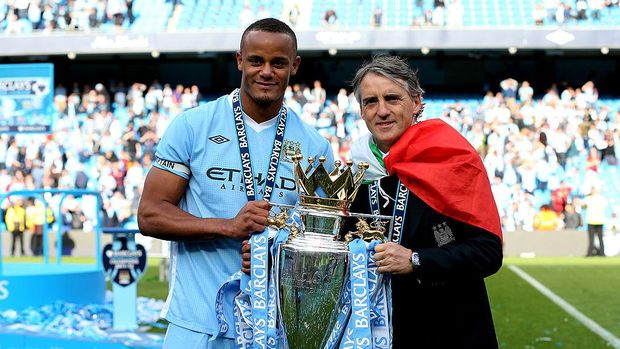 MANCHESTER, ENGLAND - MAY 13:  Vincent Kompany the captain of Manchester City and Roberto Mancini the manager of Manchester City pose with the trophy following the Barclays Premier League match between Manchester City and Queens Park Rangers at the Etihad Stadium on May 13, 2012 in Manchester, England.  (Photo by Alex Livesey/Getty Images)