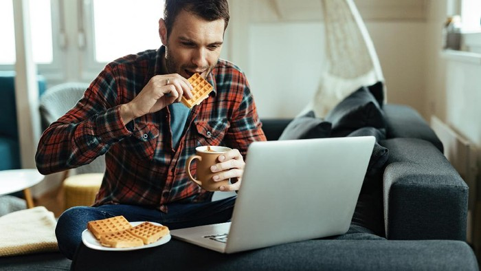 Smiling man using laptop while drinking coffee and eating waffle in the living room.