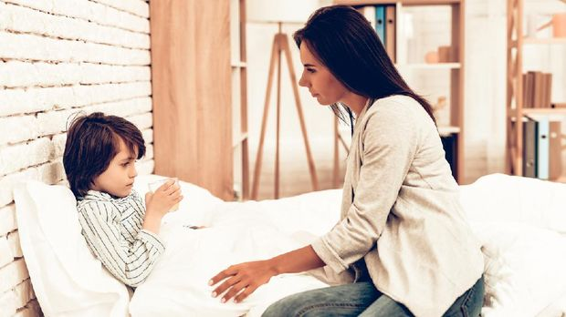 Mother Giving Medicine to Sick Son Lying Bed. Caring Mom Giving Sick Boy Pills. Worried Mother Giving Glass of Water to Ill Kid. Hospital Concept. Healthy Concept. Parent Concept.