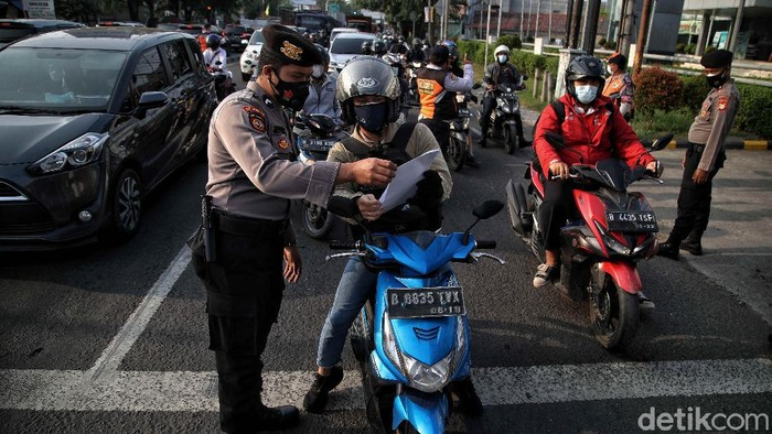 Petugas gabungan memeriksa dokumen pegendara motor dan mobil arah ke Jakarta di Pos Pegendalian Mobilitas  PPKM Darurat di kawasan Jalan Medan Satria, Bekasi, Jawa Barat, Jumat (16/7/2021).