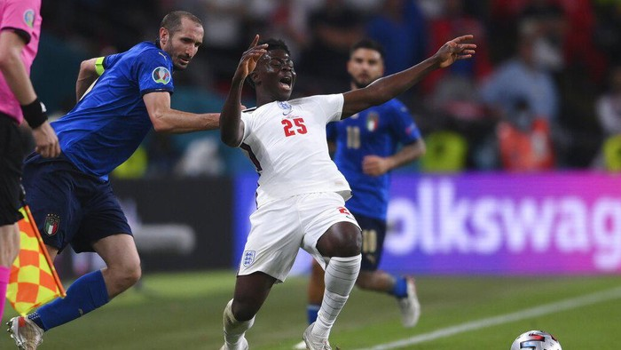 Italys Giorgio Chiellini, left, stops Englands Bukayo Saka during the Euro 2020 soccer final match between England and Italy at Wembley stadium in London, Sunday, July 11, 2021. (Laurence Griffiths/Pool via AP)