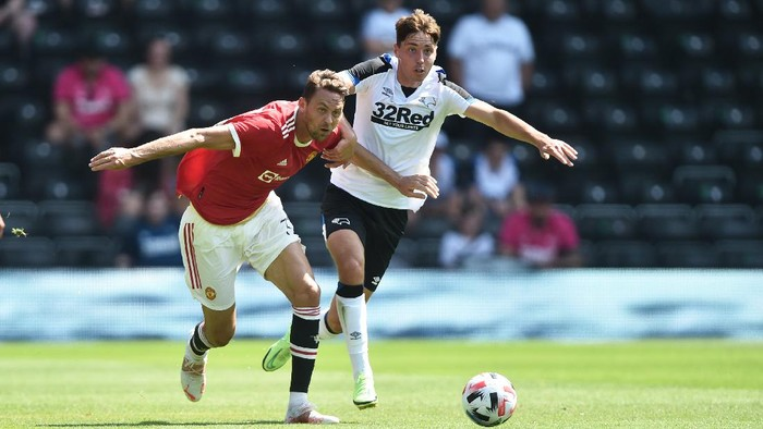 DERBY, ENGLAND - JULY 18: Nemanja Matic of Manchester United and Isaac Hutchinson of Derby compete for the ball during the pre-season friendly match between Derby County and Manchester United at Pride Park on July 18, 2021 in Derby, England. (Photo by Nathan Stirk/Getty Images)