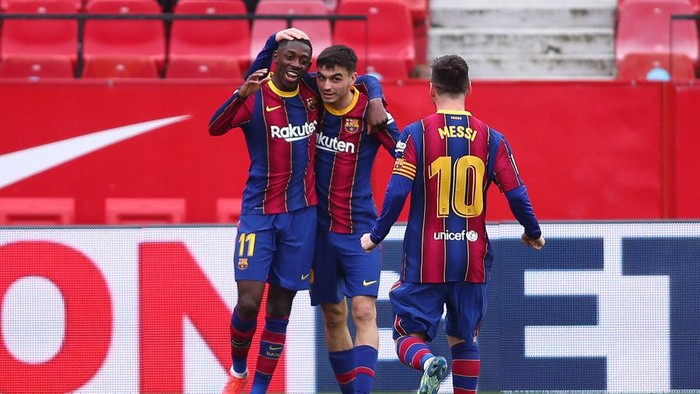 SEVILLE, SPAIN - FEBRUARY 27: Ousmane Dembele of FC Barcelona celebrates with team mates Pedri and Lionel Messi after scoring their sides first goal during the La Liga Santander match between Sevilla FC and FC Barcelona at Estadio Ramon Sanchez Pizjuan on February 27, 2021 in Seville, Spain. Sporting stadiums around Spain remain under strict restrictions due to the Coronavirus Pandemic as Government social distancing laws prohibit fans inside venues resulting in games being played behind closed doors. (Photo by Fran Santiago/Getty Images)