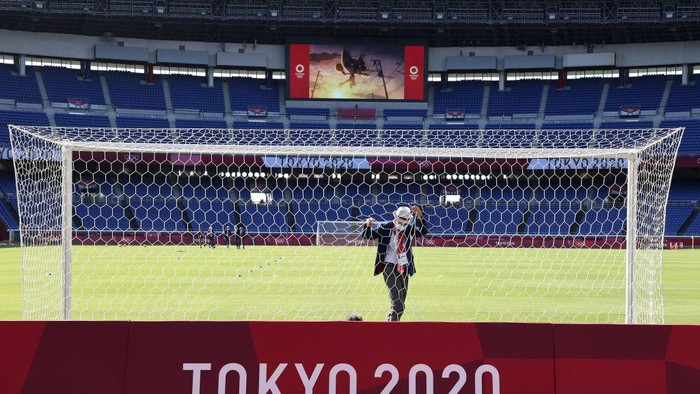 YOKOHAMA, JAPAN - JULY 22: A match official is seen checking the net prior to the Mens First Round Group D match between Cote dIvoire and Saudi Arabia during the Tokyo 2020 Olympic Games at International Stadium Yokohama on July 22, 2021 in Yokohama, Kanagawa, Japan. (Photo by Toru Hanai/Getty Images)