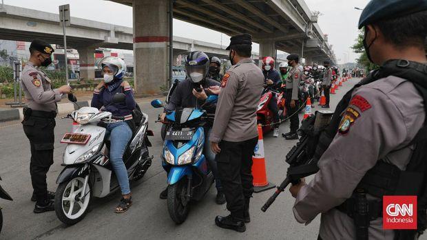 Petugas polisi dan TNI memeriksa surat STRP warga yang akan melintasi penutupan jalan di kawasan Pondok Kelapa, Jakarta. Tidak ada perubahan ruas jalan yang ditutup pada PPKM Level 4. CNNIndonesia/Safir Makki