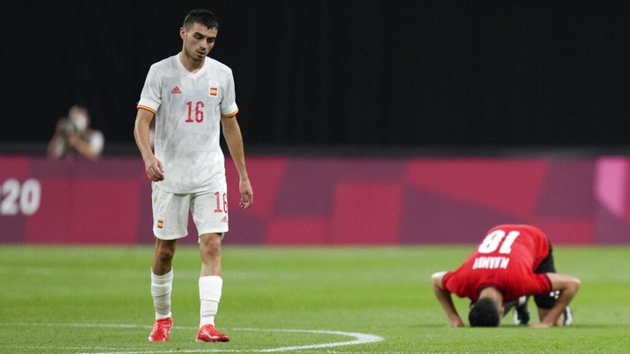 Spains Pedri Gonzalez walks off the field as Egypts Mahmoud El Wench kneels at the end of their 0-0 draw during a mens soccer match at the 2020 Summer Olympics, Thursday, July 22, 2021, in Sapporo, Japan. (AP Photo/SIlvia Izquierdo)