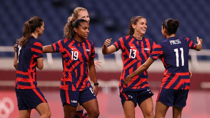 SAITAMA, JAPAN - JULY 24: Alex Morgan #13 of Team United States celebrates with Catarina Macario #19 and Christen Press #11 after scoring their sides fifth goal during the Womens First Round Group G match between New Zealand and United States on day one of the Tokyo 2020 Olympic Games at Saitama Stadium on July 24, 2021 in Saitama, Japan. (Photo by Francois Nel/Getty Images)