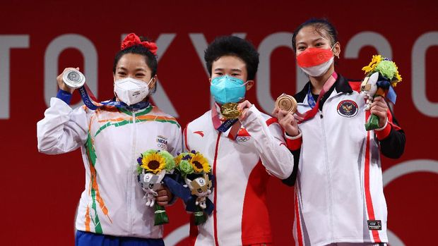 Tokyo 2020 Olympics - Weightlifting - Women's 49kg - Medal Ceremony - Tokyo International Forum, Tokyo, Japan - July 24, 2021. Gold medalist Hou Zhihui of China, Silver medalist Mirabai Chanu Saikhom of India and Bronze medalist Windy Cantika Aisah of Indonesia pose. REUTERS/Edgard Garrido