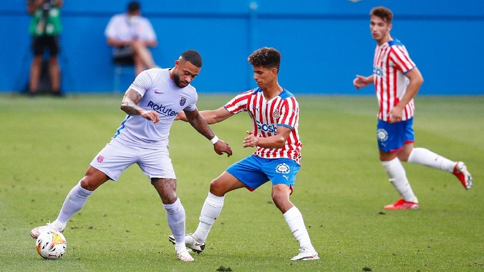 BARCELONA, SPAIN - JULY 24: Memphis Depay of FC Barcelona challenges for the ball against Ilyas Saira of Girona FC during the pre-season friendly match between FC Barcelona and Girona at Estadi Johan Cruyff on July 24, 2021 in Barcelona, Spain. (Photo by Eric Alonso/Getty Images)