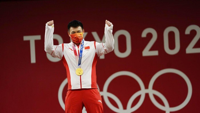 Chen Lijun of <a href='https://manado.tribunnews.com/tag/china' title='China'>China</a> celebrates on the podium after winning the gold medal and setting an Olympic record in the mens 67kg weightlifting event, at the 2020 Summer Olympics, Sunday, July 25, 2021, in Tokyo, Japan. (AP Photo/Luca Bruno)