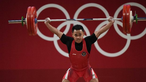 Eco Yuli Irawan of Indonesia competes in the men's 61kg weightlifting event, at the 2020 Summer Olympics, Sunday, July 25, 2021, in Tokyo, Japan. (AP Photo/Luca Bruno)