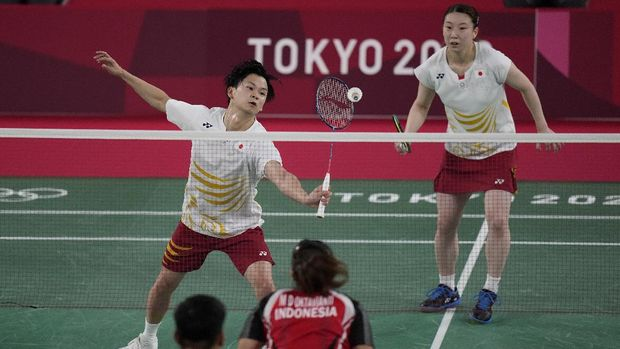 Japan's Yuta Watanabe and Arisa Higashino play against Indonesia's Praveen Jordan and Melati Daeva Oktavianti during their mixed doubles group play stage badminton match at the 2020 Summer Olympics, Monday, July 26, 2021, in Tokyo, Japan. (AP Photo/Markus Schreiber)