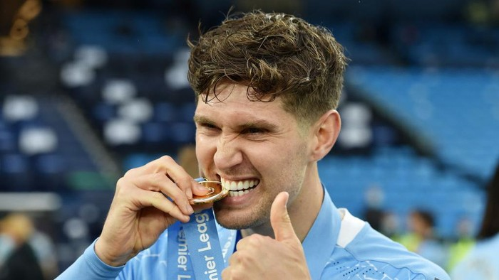 MANCHESTER, ENGLAND - MAY 23: John Stones of Manchester City bites his Premier League Winners' medal as Manchester City are presented with the Trophy as they win the league following the Premier League match between Manchester City and Everton at Etihad Stadium on May 23, 2021 in Manchester, England. A limited number of fans will be allowed into Premier League stadiums as Coronavirus restrictions begin to ease in the UK. (Photo by Peter Powell - Pool/Getty Images)