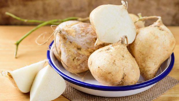 Fresh jicama or yam in bowl on wooden background