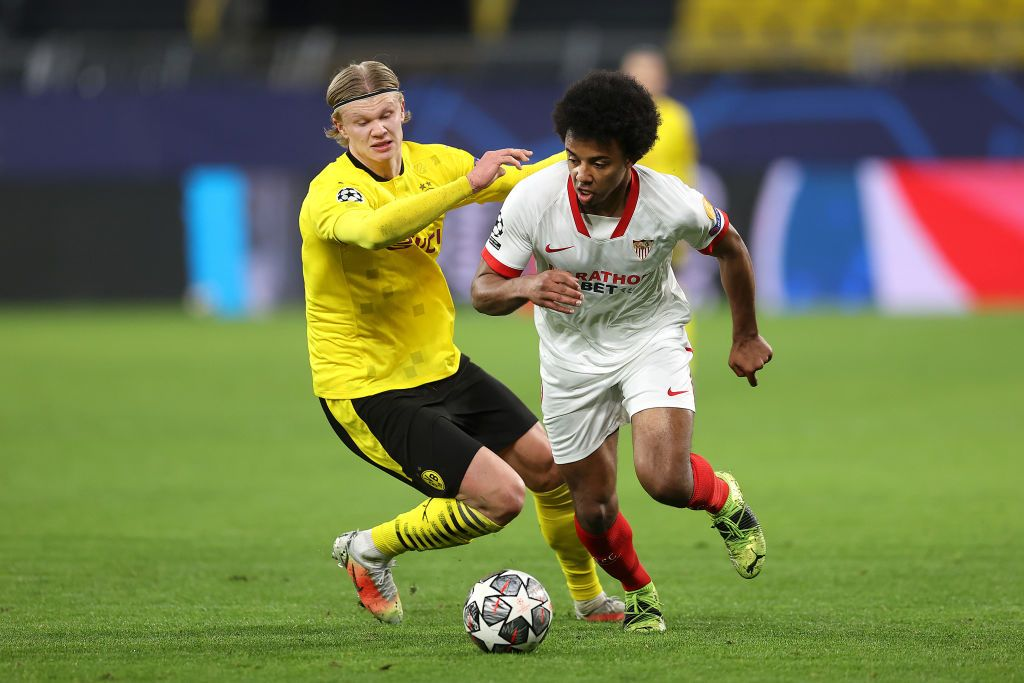 DORTMUND, GERMANY - MARCH 09: Jules Kounde of Sevilla battles for possession with Erling Haaland of Borussia Dortmund during the UEFA Champions League Round of 16 match between Borussia Dortmund and Sevilla FC at Signal Iduna Park on March 09, 2021 in Dortmund, Germany. Sporting stadiums around Germany remain under strict restrictions due to the Coronavirus Pandemic as Government social distancing laws prohibit fans inside venues resulting in games being played behind closed doors. (Photo by Lars Baron/Getty Images)